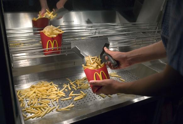 ARCHIVBILD ZUR BEKANNTGABE DES 4. QUARTALSERGEBNISSES VON MC DONALDS, AM MONTAG, 23. JANUAR 2017 - Ein Mitarbeiter von McDonald's fuellt am 21. August 2007 in der Filiale in Regensdorf Pommes frites in eine Kartonschachtel ab. (KEYSTONE/Gaetan Bally)  An employee of McDonald's fills french fries into a paper bag in the branch in Regensdorf, Switzerland, pictured on August 21, 2007. (KEYSTONE/Gaetan Bally)
