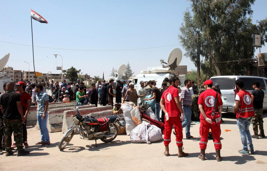 epa05530158 Volunteers of the Syrian Arab Red Crescent assist evacuees from the rebel-held al-Moadhamiyeh city in the countryside of Damascus, Syria, 08 September 2016. According to media reports, about 150 people were evacuated and will be relocated to the makeshift center in Harjalleh. The evacuation is part of a process that began a week ago to evacuate people who are originally from the adjacent Darayya suburb.  EPA/YOUSSEF BADAWI