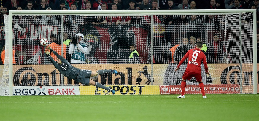 epa04696235 Munich's goalkeeper Manuel Neuer (L) saves a shot from Leverkusen's Josip Drmic during the penalty shootout of the German DFB Cup quarter final soccer match between Bayer Leverkusen and Bayern Munich at the BayArena in Leverkusen, Germany, 08 April 2015.