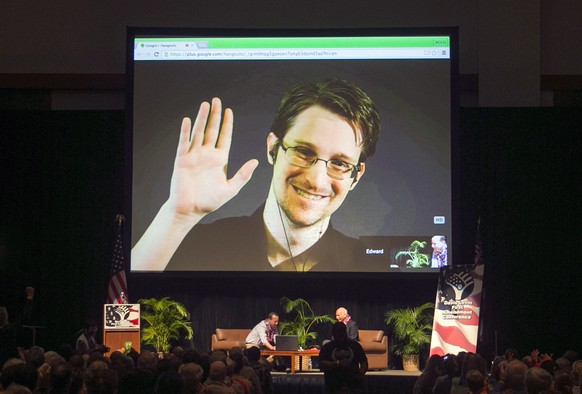 FILE - In this Feb. 14, 2015 file photo, Edward Snowden appears on a live video feed broadcast from Moscow at an event sponsored by ACLU Hawaii in Honolulu. The former National Security Agency worker, who leaked classified documents about government surveillance, started tweeting Tuesday, Sept. 29, 2015. (AP Photo/Marco Garcia, File)