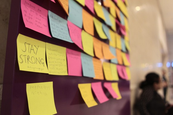 epa04542792 A post-it note reading 'Stay Strong' is attached to a board of well wishes for the passengers of the missing AirAsia flight QZ 8501, outside the relatives' holding area at Changi airport in Singapore, 30 December 2014. Floating debris, a possible fuselage, and several bodies were spotted 30 December by rescuers searching for an AirAsia plane with 162 people on board, as officials said they were nearly certain they had found the remains of flight QZ8501. AirAsia Indonesia flight QZ8501 disappeared from radar over the Java Sea after taking off from Surabaya in Indonesia's East Java province en route to Singapore on 28 December morning. AirAsia said 155 of the people on board were Indonesians. The others included three from South Korea, and one each from Singapore, Malaysia, France and Britain.  EPA/WALLACE WOON