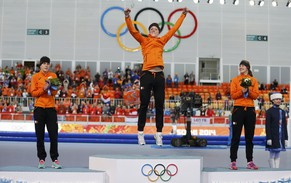 First-placed Jorien ter Mors (C) of the Netherlands jumps on the podium, as second-placed Ireen Wust (L) of the Netherlands and third-placed Lotte Van Beek (R) of the Netherlands look on, during the flower ceremony for the women's 1,500 metres speed skating event at the Adler Arena during the 2014 Sochi Winter Olympics, February 16, 2014.       REUTERS/Issei Kato (RUSSIA  - Tags: OLYMPICS SPORT SPEED SKATING)