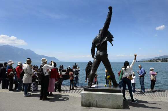 Tourists take pictures of a bronze statue of Freddie Mercury the singer of Queen after a flash mob during the first edition of the Freddie For A Day festival, in Montreux, Switzerland, Sunday, June 1, 2014. Freddie For A Day is a festival in memory of the late Freddie Mercury, lead singer of the group Queen and former Montreux resident. (KEYSTONE/Laurent Gillieron)