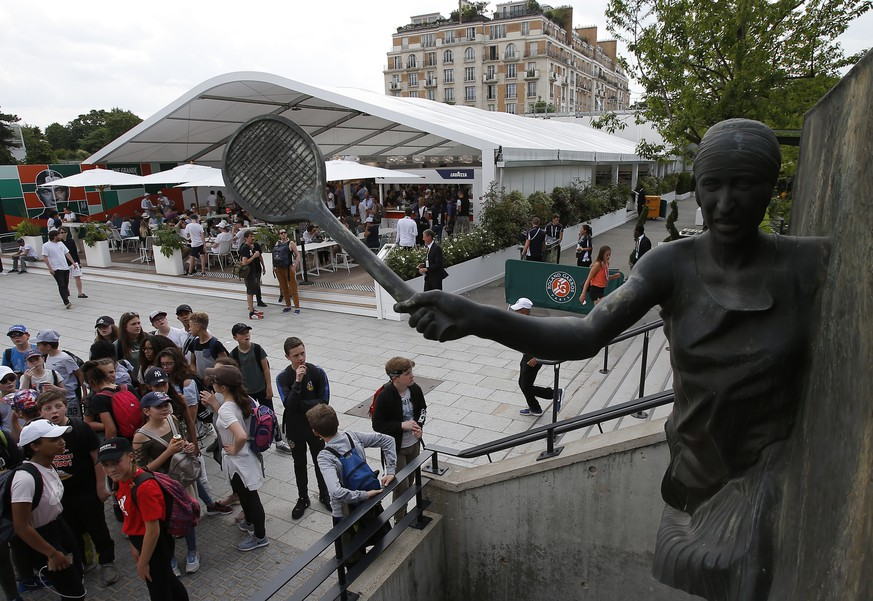 Children watch the statue of late French tennis champion Suzanne Lenglen at the Roland Garros stadium in Paris, Friday, May 25, 2018. The French Open tennis tournament starts Sunday. (AP Photo/Michel Euler)