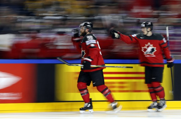 In this slow shutter speed photo, Canada's Ryan O'Reilly, left, celebrates after scoring during the Ice Hockey World Championships final match between Canada and Sweden in the LANXESS arena in Cologne, Germany, Sunday, May 21, 2017. (AP Photo/Petr David Josek)