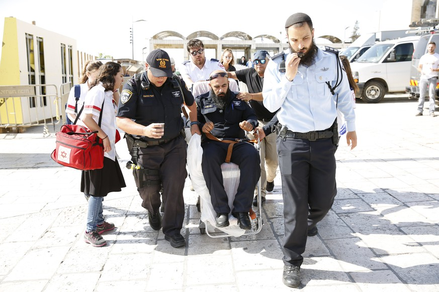 epa06086241 An Israeli policeman is evacuated from the Temple Mount compound in Jerusalem's Old City, 14 July 2017. According to police sources, three Palestinian attackers opened fire on police forces at the Temple Mount compound wounding two Israeli policemen. The Three attackers were killed by police officers, and a third police officer was reportedly injured by shapnel.  EPA/ABIR SULTAN