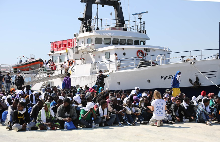 Migrants sit on the ground after disembarking from the Migrant Offshore Aid Station vessel ' Phoenix ' in the harbor of Augusta, Sicily, Southern Italy, Saturday, May 9, 2015. European Union plans to introduce a quota system obliging countries to share the burden of settling refugees unraveled Friday as member nations began rejecting the scheme. (AP Photo/Francesco Malavolta)