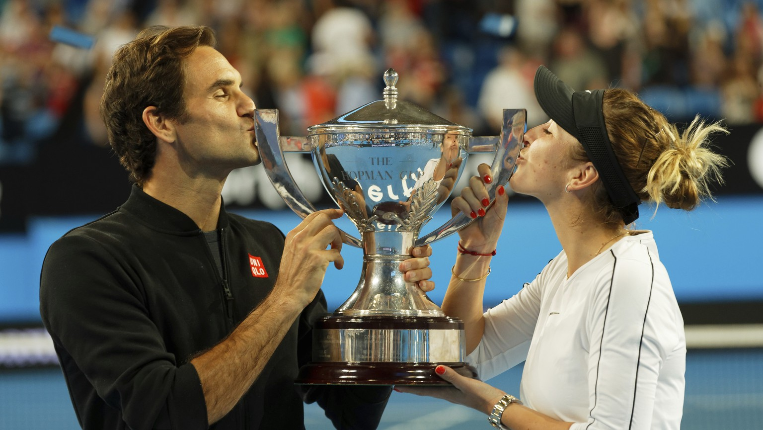 Switzerland's Roger Federer and Belinda Bencic kiss the trophy after winning the final against Alexander Zverev and Angelique Kerber of Germany at the Hopman Cup in Perth, Australia, Saturday Jan. 5, 2019. (AP Photo/Trevor Collens)