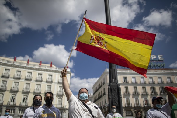 People wave Spanish flags as people hold a minute of silence for the victims of COVID-19 at Sol square in downtown Madrid, Spain, Wednesday, June 3, 2020. Spain's Health Ministry says it recorded no deaths from COVID-19 Wednesday for a second day in a row. (AP Photo/Manu Fernandez)