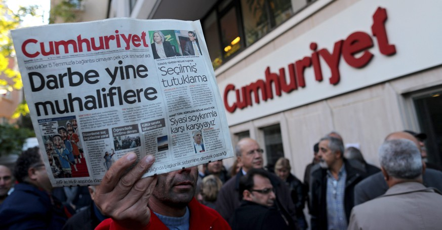 epa05611508 A man holds a 31 October 2016 copy of Cumhuriyet newspaper headlining 'Coup against opposition' in front of the headquarter of Cumhuriyet daily newspaper in Istanbul, Turkey 31 October 2016. Turkish police detained the editor-in-chief Murat Sabuncu, columnist Hikmet Cetinkaya of the opposition newspaper Cumhuriyet in Istanbul and 13 arrest warrants have been issued for journalists and executives during an police operation.  EPA/SEDAT SUNA