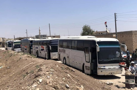 In this photo released by the Syrian official news agency SANA, buses arrive in Tel el-Eis, the crossing between Aleppo and Idlib provinces, Syria, Wednesday, July 18, 2018. About 7,000 Syrians were expected to be evacuated from the two pro-government villages of Foua and Kfarya, ending their three-year siege by insurgents who control the surrounding areas. (SANA via AP)