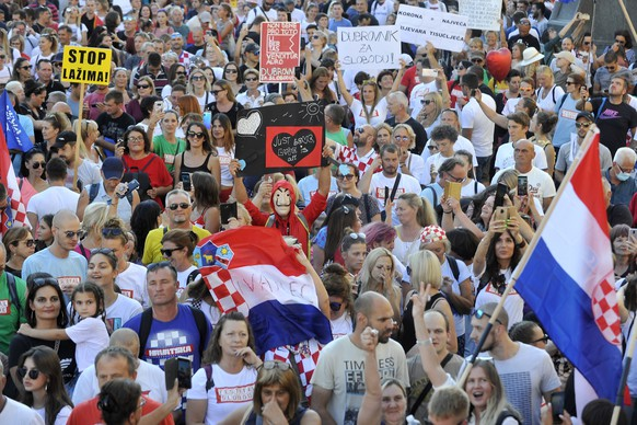 Protesters hold placards during a protest in central Zagreb, Croatia, Saturday, Sept. 5, 2020. Several thousand gathered to protest against government measures against spreading of the Covid-19 virus. (AP Photo)