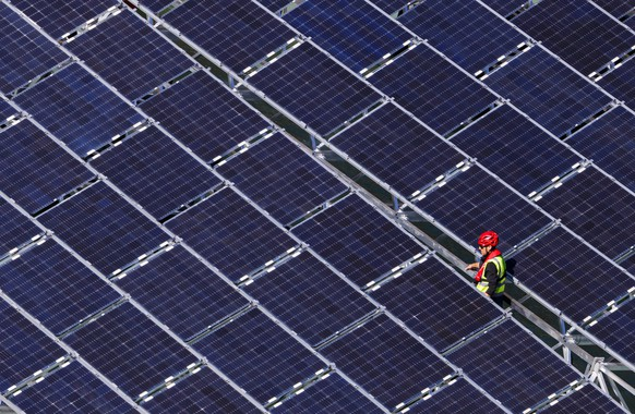 epa07906927 A worker assembles floating barges with solar panels on the Lac des Toules, an alpine reservoir lake, in Bourg-Saint-Pierre, Switzerland, 08 October 2019 (issued 09 October 2019) Upon completion the floating solar panel station will consist of 36 floating barges featuring 2'240 square meters of solar cells targeting to deliver 800'000 kilowatt-hour per year, the annual power consumption of approximately 220 homes.  EPA/VALENTIN FLAURAUD  ATTENTION: This Image is part of a PHOTO SET
