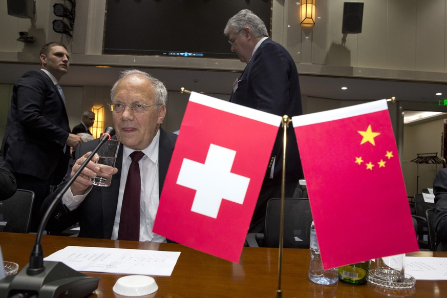 Switzerland's Federal President Johann Schneider-Ammann drinks from a glass near Swiss and Chinese national flags during a meeting at the head office of the China Construction Bank in Beijing Thursday, April 7, 2016. (AP Photo/Ng Han Guan)