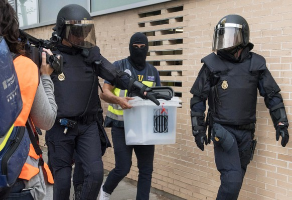 epa06238250 Spanish National Police officers seize a ballot box during a raid at a health clinic during the '1-O Referendum' in Cappont, Lleida, Catalonia, northeastern Spain, on 01 October 2017. National Police officers and Civil guards have been deployed to seize voting material and to prevent the people from entering to the polling centers and vote in the Catalan independence referendum, that has been banned by the Spanish Constitutional Court, what has provocked clashes between pro-independence people and the police forces in some polling centers.  EPA/Adria Ropero
