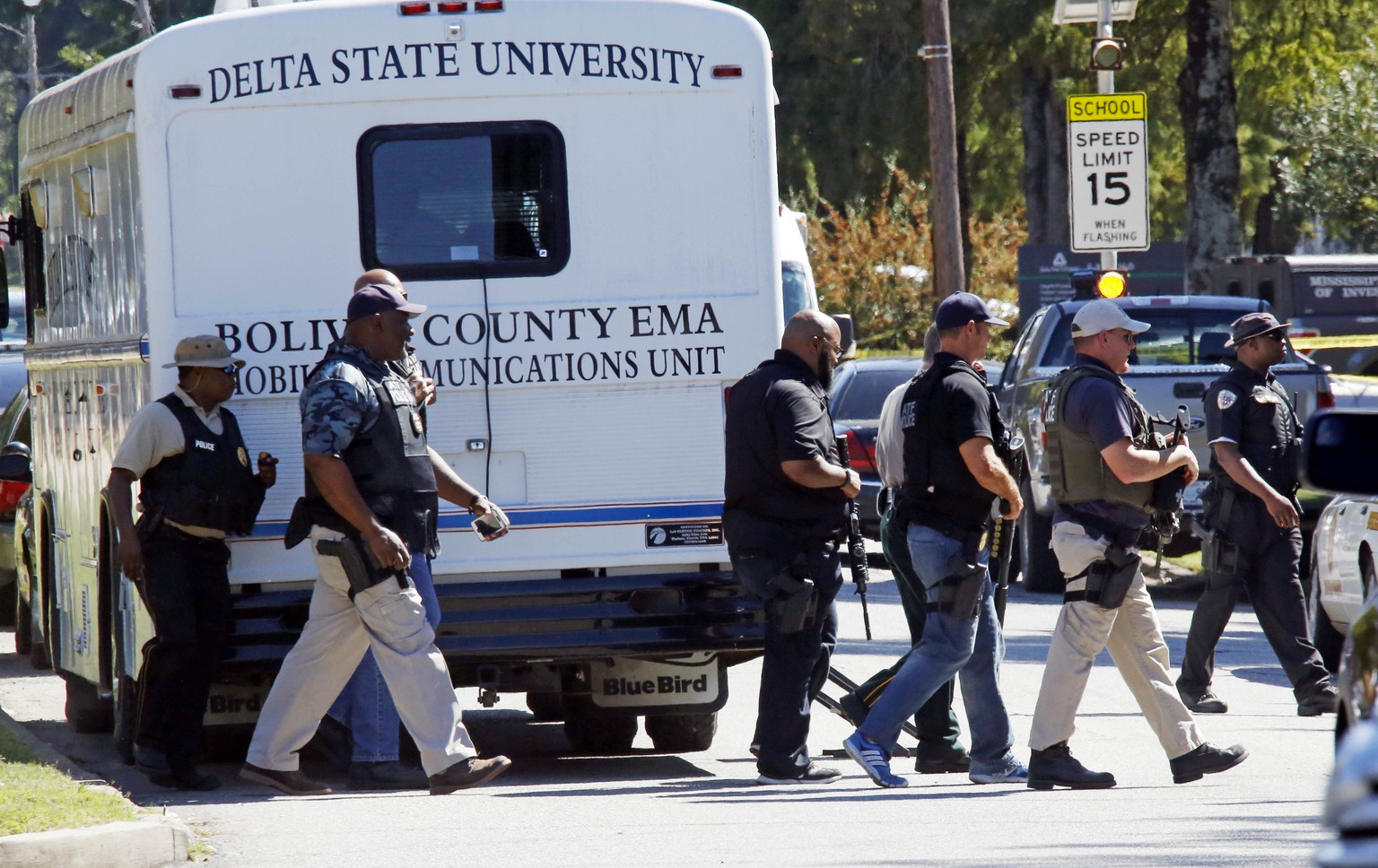 Law enforcement walk across the Delta State University campus to search for an active shooter in connection with a the shooting of history professor Ethan Schmidt in his office in Cleveland, Miss., Monday, Sept. 14, 2015. (AP Photo/Rogelio V. Solis)