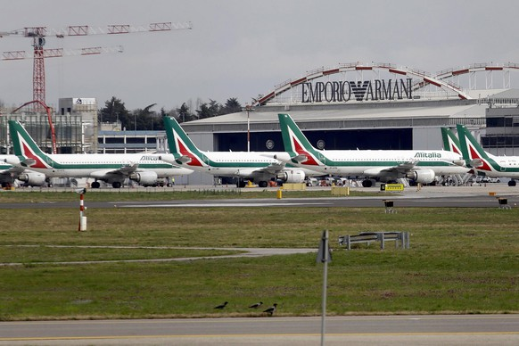 epa08291785 Aircraft of the Italian flag carrier Alitalia remain docked at the deserted Milan Linate Airport amid the coronavirus pandemic in Milan, northern Italy, 13 March 2020. The airport, Milan's third-largest, has been temporarily closed down following a decree issued by the Ministry of Transport. All commercial and general passenger air traffic will be concentrated on Milan's Malpensa airport. According to the latest figures confirmed by Italian authorities, there are at least 15,113 cases of infection with the COVID-19 disease caused by the SARS-CoV-2 coronavirus and around 1,016 deaths so far in the Mediterranean country.  EPA/MOURAD BALTI TOUATI