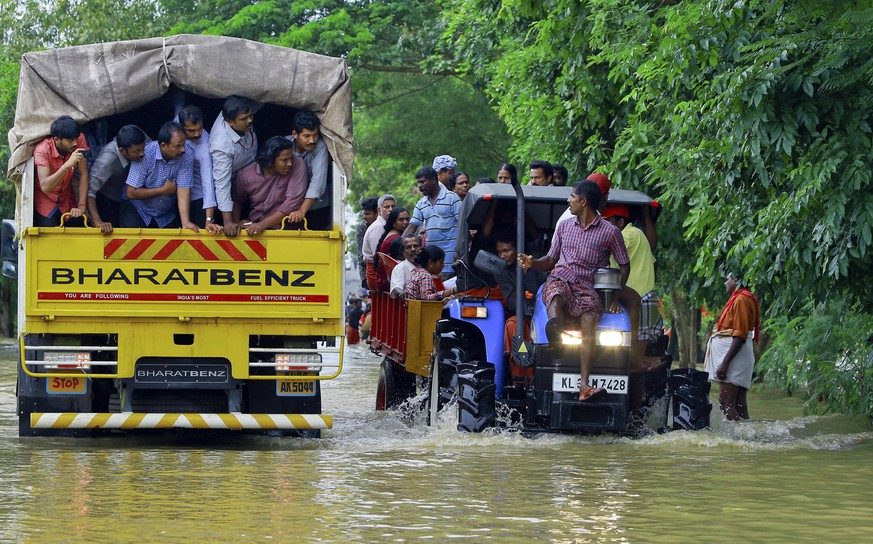 Flood affected people are rescued in a tractor, right as volunteers go for rescue work in a truck, left, at Kainakary in Alappuzha district, Kerala state, India, Friday, Aug. 17, 2018. Rescuers used helicopters and boats on Friday to evacuate thousands of people stranded on their rooftops following unprecedented flooding in the southern Indian state of Kerala that killed more than 320 people in the past nine days, officials said. (AP Photo/Tibin Augustine)