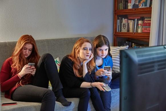 [Symbolic Image, Staged Picture, ] Sisters sitting on a couch in the living room use their smart phones while watching TV, photographed in Lucerne, Switzerland, on December 13, 2015. (KEYSTONE/Christof Schuerpf)  [Gestellte Aufnahme, Symbolbild, ] Geschwister benutzen ihre Smartphones waehrend sie im Wohnzimmer auf dem Sofa sitzend fersehen, aufgenommen am 13. Dezember 2015 in Luzern. (KEYSTONE/Christof Schuerpf)
