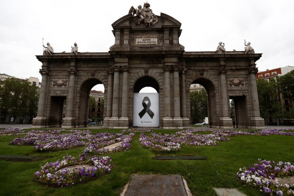 epa08378712 A black ribbon is displayed at at the Puerta de Alcala monument in memory of coronavirus fatalities, in downtown Madrid, Spain, 23 April 2020. Local authorities observed a minute silence for victims as Spain faces its 40th day of lock down.The country is under a lock down to avoid the spreading COVID-19 disease caused by the SARS-CoV-2 coronavirus.  EPA/Mariscal