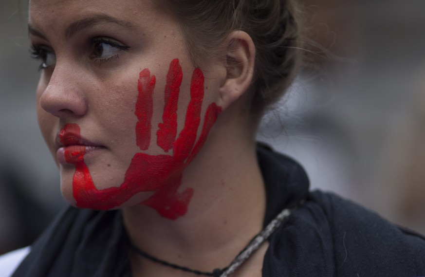 A woman with a red hand painted on her face participates in a demonstration against gender violence in Rio de Janeiro, Brazil, Tuesday, Oct. 25, 2016. Women in Brazil organized protests condemning violence against women following the brutal gang rape of a woman on the outskirts of Rio de Janeiro by suspected drug dealers. (AP Photo/Leo Correa)