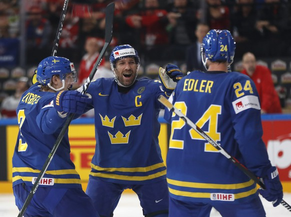 Sweden's Alexander Edler, right, celebrates with Joel Lundqvist, center, and John Klingberg, left, after scoring a goal during the Ice Hockey World Championships quarterfinal match between Switzerland and Sweden in the AccorHotels Arena in Paris, France, Thursday, May 18, 2017. (AP Photo/Petr David Josek)