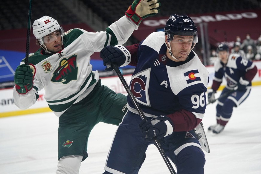 Colorado Avalanche right wing Mikko Rantanen, front, fends off Minnesota Wild left wing Kevin Fiala as they pursue the puck in the second period of an NHL hockey game Wednesday, Feb. 24, 2021, in Denver. (AP Photo/David Zalubowski) r m