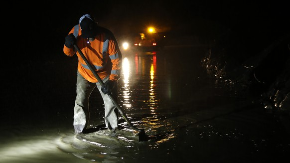 Butte County road worker Matt Brandt clears a drain pump of debris from a mudslide that partially blocked Honey Run Road, Thursday, Nov. 29, 2018, near Chico, Calif. Flash flooding hit Chico and nearby wildfire-scarred Paradise causing flooding and mudslides forcing officials to deploy swift water rescue teams to rescue people stuck in vehicle and from homes. (AP Photo/Rich Pedroncelli)