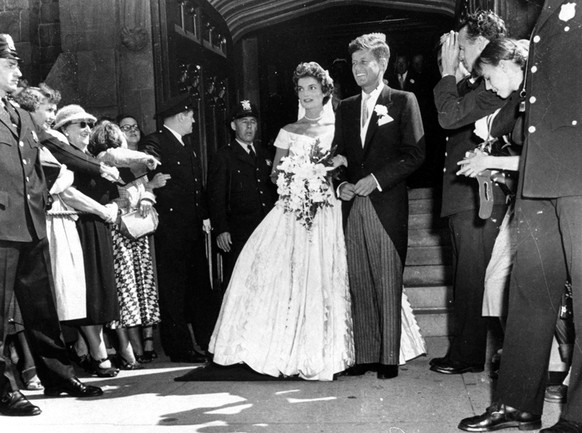FILE - In this Sept 12, 1953 file photo, Senator John F. Kennedy, D-Mass., leaves St. Mary's Church with his bride, the former Jacqueline Bouvier, after their wedding in Newport, R.I. The church where the couple was married is being restored in 2016 to the appearance it had on their wedding day.  (AP Photo/File)