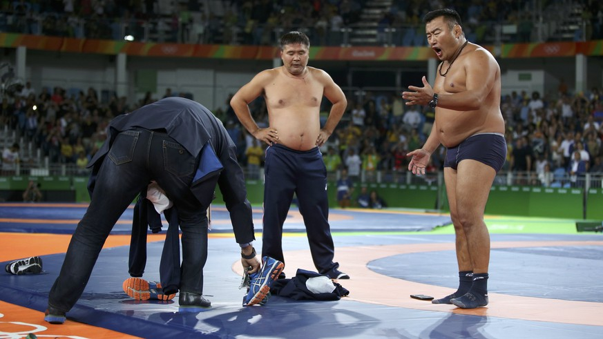 2016 Rio Olympics - Wrestling - Final - Men's Freestyle 65 kg Bronze - Carioca Arena 2 - Rio de Janeiro, Brazil - 21/08/2016. The coach (R) of Mandakhnaran Ganzorig (MGL) of Mongolia stands undressed as he protests after the match against Ikhtiyor Navruzov (UZB) of Uzbekistan. REUTERS/Toru Hanai FOR EDITORIAL USE ONLY. NOT FOR SALE FOR MARKETING OR ADVERTISING CAMPAIGNS.