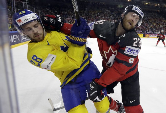 Sweden's Elias Lindholm, left, challenges with Canada's Claude Giroux during the Ice Hockey World Championships final match between Canada and Sweden in the LANXESS arena in Cologne, Germany, Sunday, May 21, 2017. (AP Photo/Petr David Josek)