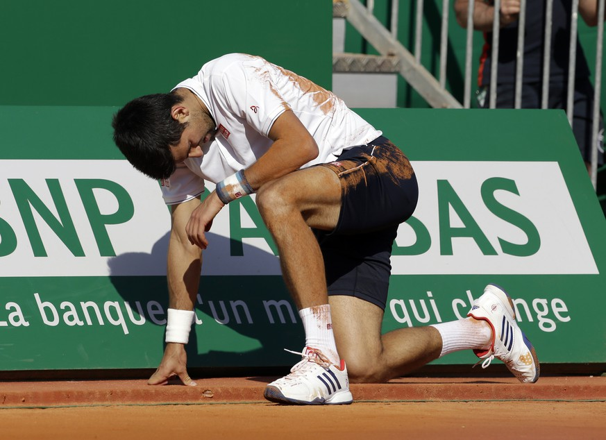 Serbia's Novak Djokovic falls, during their quarterfinal match of the Monte Carlo Tennis Masters tournament against Belgium's David Goffin, in Monaco, Friday, April, 21, 2017. (AP Photo/Claude Paris)