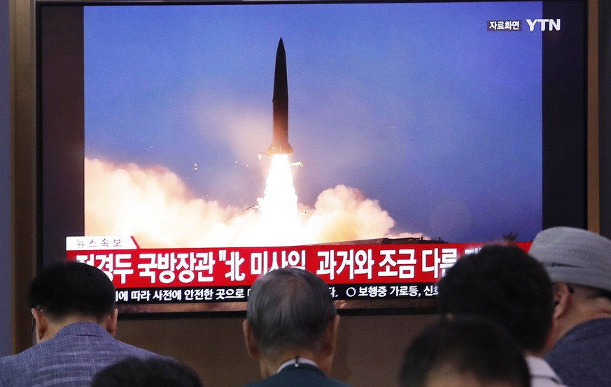 People watch a TV showing a file image of North Korea's missile launch during a news program at the Seoul Railway Station in Seoul, South Korea, Wednesday, July 31, 2019. North Korea on Wednesday fired several unidentified projectiles off its east coast, South Korea's military said, less than a week after the North launched two short-range ballistic missiles into the sea in a defiance of U.N. resolutions. The signs read: