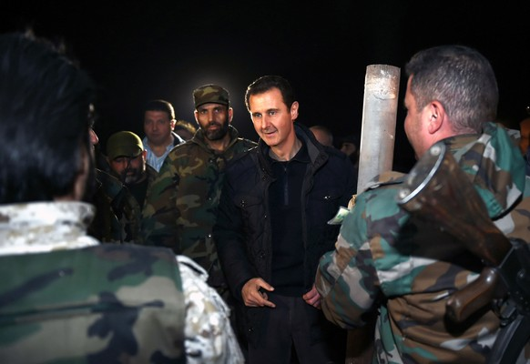 In this Wednesday, Dec. 31, 2014 photo released by the Syrian official news agency SANA, Syrian President Bashar Assad, center, speaks with Syrian troops during his visit on the front line in the eastern Damascus district of Jobar, Syria. Assad has made a rare visit to the front line of his country's civil war, spending New Year's Eve with his troops in a tense eastern Damascus neighborhood. (AP Photo/SANA)