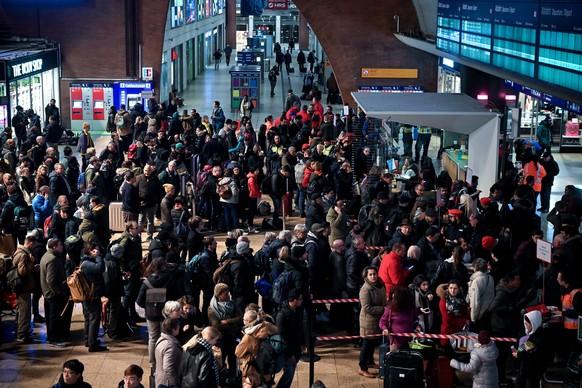 Passagiere, die am Hauptbahnhof Köln festsitzen, stehen an, um sich beim Infopersonal der DB zu informieren.