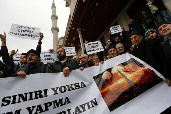 Demonstrators hold a placard depicting Kouachi brothers at the courtyard of Fatih mosque during a protest in Istanbul January 16, 2015. Turkish Islamist groups gathered at Fatih mosque to hold a special prayer for Kouachi brothers who carried out the Charlie Hebdo attack in Paris last week. The full sentence on the big banner reads: 'If your freedom of expression has no limits, prepare yourselves for us to use our right to protest limitlessly.' The texts on small banners read 'We are all Said Kouachi' and 'We are all Cherif Kouachi'.  REUTERS/Murad Sezer (TURKEY  - Tags: CRIME LAW POLITICS CIVIL UNREST)