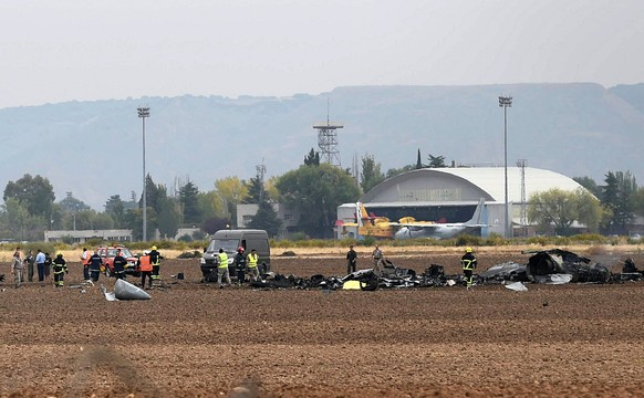 epa06270582 Members from the Emergency Services walk among the fuselage of aSpanish Airf Forces McDonnell Douglas F/A-18 Hornet as it crashed near the Air Base in Torrejon de Ardoz, Madrid, Spain, 17 October 2017. The causes of the accident, in which the pilot died  are still unclear.  EPA/FERNANDO VILLAR