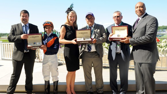 IMAGE DISTRIBUTED FOR LONGINES - New York Yankees legend Bernie Williams, right, and Sebastien Zbinden, left, and Jennifer Judkins, both of Longines, present watches from the Longines Conquest Classic collection to jockey Javier Castellano, trainer Brian Lynch, second right, and owner representative Bob Feld, center, after their horse Coffee Clique won the $500,000 Longines Just a Game Stakes, Saturday, June 7, 2014, at Belmont Park in New York.  Longines, the Swiss watchmaker known for its elegant timepieces, is the Official Watch and Timekeeper of the 146th running of the Belmont Stakes. (Photo by Diane Bondareff/Invision for Longines/AP Images)