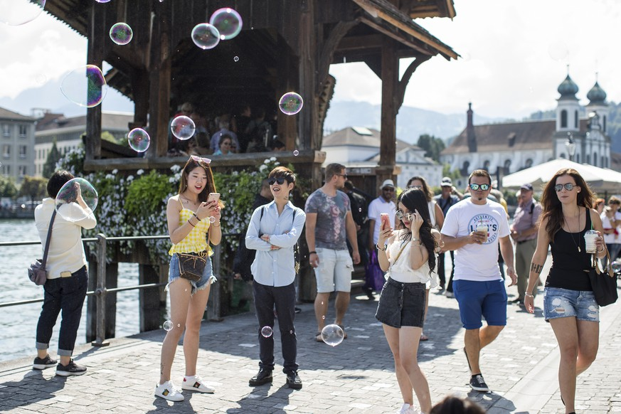ARCHIV - ZUR TOURISMUSSTATISTIK UND DER ZUNAHME VON LOGIERNAECHTEN IN DER SCHWEIZ STELLEN WIR IHNEN DIESE BILDREPORTAGE ZUR VERFUEGUNG - Soap bubbles and and tourist with the Kappelbruecke bridge in the background in Lucerne, Switzerland, on August 14, 2017. In the city of Lucerne counts between 8 and 10 million day visitors a year. (KEYSTONE/Alexandra Wey) 