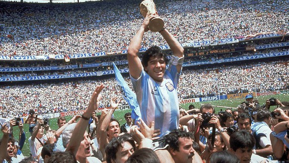 FILE - In this June 29, 1986, file photo, Diego Maradona, holds up the trophy, after Argentina beat West Germany 3-2 in their World Cup soccer final match, at the Atzeca Stadium, in Mexico City. On Sunday, July 13, 2014, Germany and Argentina will face each other again in the final of the 2014 soccer World Cup.(AP Photo/Carlo Fumagalli, File)