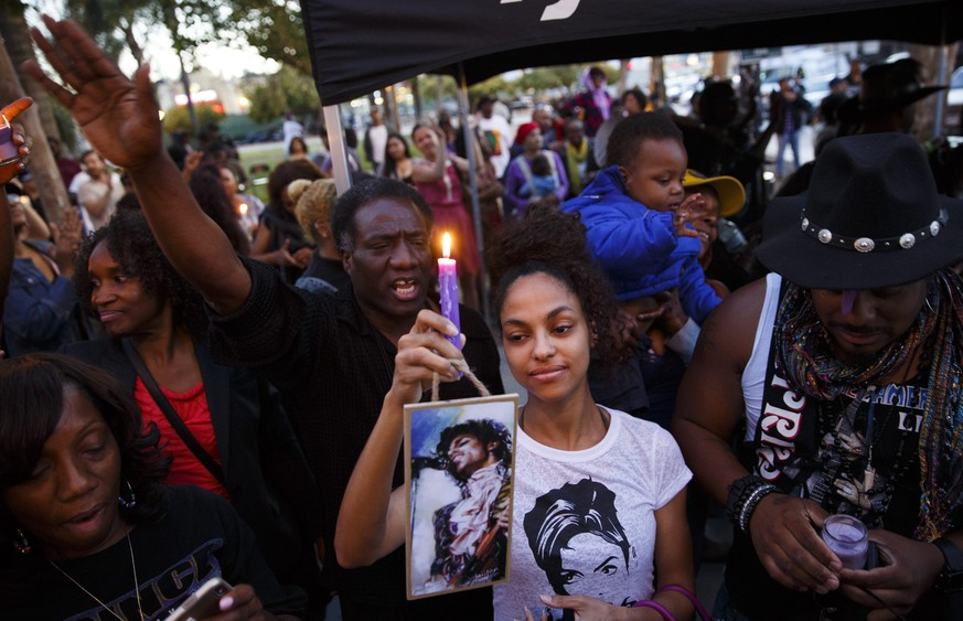 epaselect epa05271408 Mourners pay tribute to musician Prince during a vigil in Los Angeles, California, 21 April 2016. American singer-songwriter and musician Prince, a multi-talented artist who produced a string of genre-fusing hits in the 1980s, died on 21 April at his residence in Chanhassen, Minnesota. He was 57.  EPA/EUGENE GARCIA