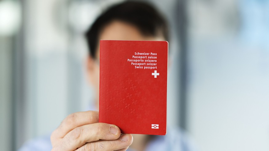 Ein Mann haelt einen biometrischen Schweizer Pass in der Hand, aufgenommen am 10. Februar 2014 in Bern. (KEYSTONE/Christian Beutler)  A man holds a Swiss biometric passport, pictured in Bern, Switzerland, February 10, 2014. (KEYSTONE/Christian Beutler)