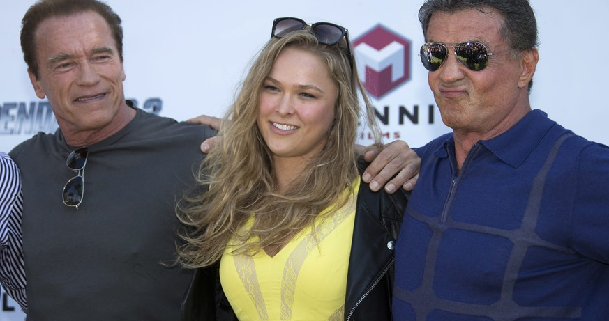 epa04212015 (L-R) US actor Arnold Schwarzenegger, US martial artist Ronda Rousey and US actor Sylvester Stallone arrive on a tank for a photocall for 'The Expendables 3' at the 67th annual Cannes Film Festival, in Cannes, France, 18 May 2014. The festival runs from 14 to 25 May.  EPA/IAN LANGSDON