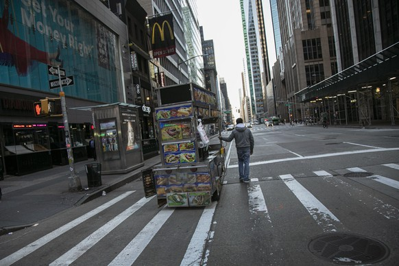 A food truck vendor pushes his cart down an empty street near Times Square in New York, on Sunday, March 15, 2020. President Donald Trump on Sunday called on Americans to cease hoarding groceries and other supplies, while one of the nation's most senior public health officials called on the nation to act with more urgency to safeguard their health as the coronavirus outbreak continued to spread across the United States. (AP Photo/Wong Maye-E)