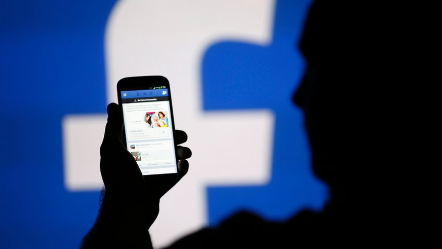 A man is silhouetted against a video screen with an Facebook logo as he poses with an Samsung smartphone in this photo illustration taken in the central Bosnian town of Zenica in a file photo taken August 14, 2013.  Facebook Inc will buy fast-growing mobile-messaging startup WhatsApp for $19 billion in cash and stock, as the world's largest social network looks for ways to boost its popularity, especially among a younger crowd. REUTERS/Dado Ruvic/Files   (BOSNIA AND HERZEGOVINA - Tags: BUSINESS TELECOMS)