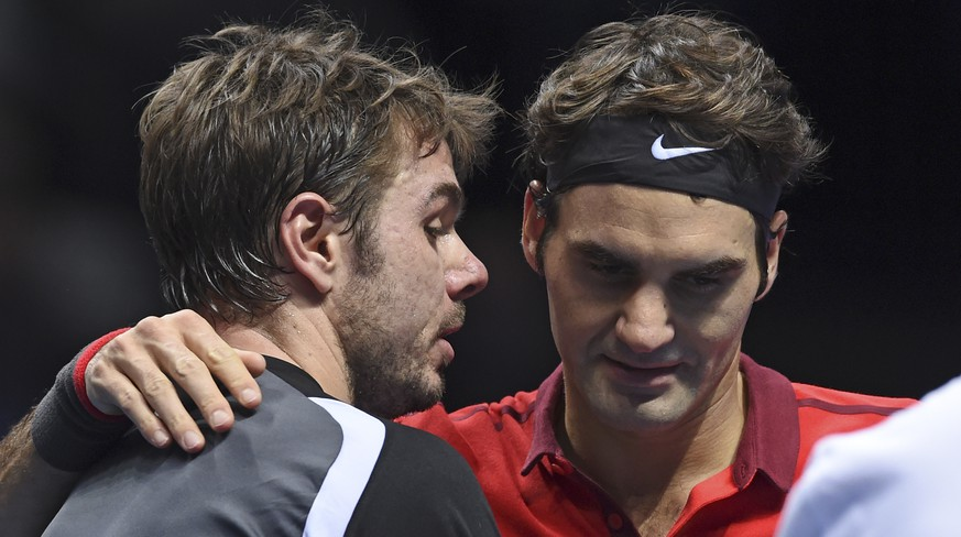 Switzerland's Stan Wawrinka, left, shakes hands with his fellow countryman Roger Federer after Federer won their ATP World Tour Finals semifinal tennis match at the O2 Arena in London, England, Saturday, Nov. 15, 2014. (AP Photo/Tim Ireland)