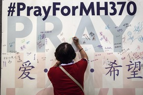 epa04253425 (FILE) A file photo dated 06 April 2014 showing A Buddhist woman writing a message ahead of a mass prayer for the missing passengers of Malaysian Airlines flight MH370, in Kuala Lumpur, Malaysia. Reports on 13 June 2014 state some  families of missing passengers of Malaysian Airlines flight MH370 have started to receive partial compensation payments amounting 50,000 USD. Six families from Malaysia and one family from China have been paid, while insurance companies probe the claims of additional 40 families from China. No trace has been found of the plane that went missing 08 March 2014.  EPA/AZHAR RAHIM