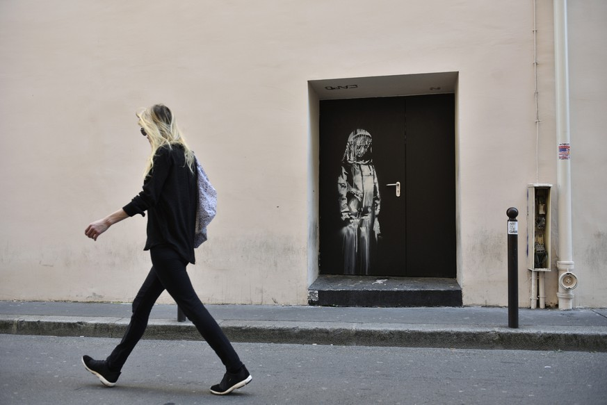 epa06841325 A recent artwork believed to be attributed to Banksy is of a woman veiled in mourning next to the Bataclan concert venue in Paris, France, 26 June 2018. Several artworks attributed to the anonymous British street artist appeared in the French capital.  EPA/JULIEN DE ROSA
