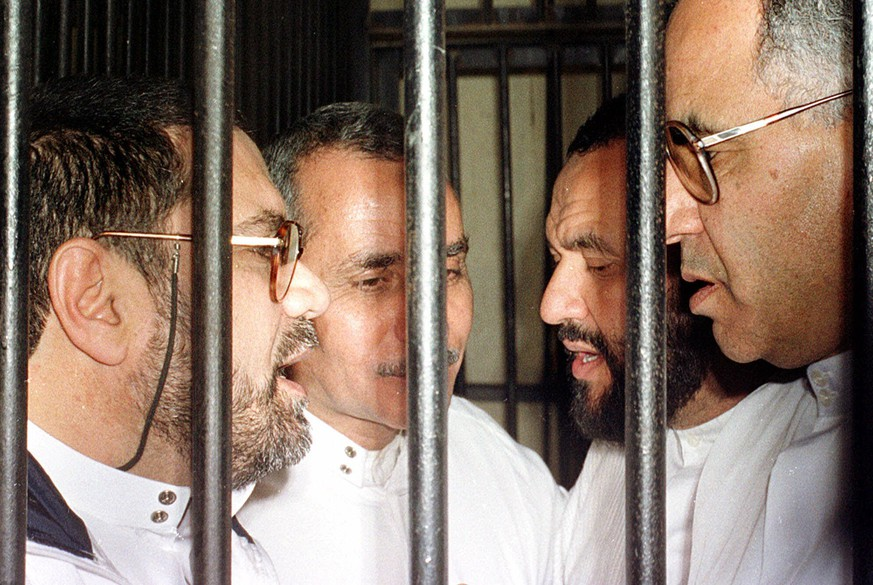 FILE - In this Sunday, Nov. 19, 2000 file photo, Egyptian Muslim Brotherhood members, from left to right, Mukhtar Nouh, Khaled Badawi, Mohammed Badi and Mohammed Ali Bishr talk behind bars at a military court in Cairo, Egypt when an Egyptian military court convicted 15 members of the outlawed for their activities with a group bent on bringing Islamic law to Egypt. A security official said Thursday, Nov. 20, 2014 Egyptian authorities have arrested Mohammed Ali Bishr, a leading Muslim Brotherhood member who played key role in negotiations between his now-banned group and the government. (AP Photo, File)