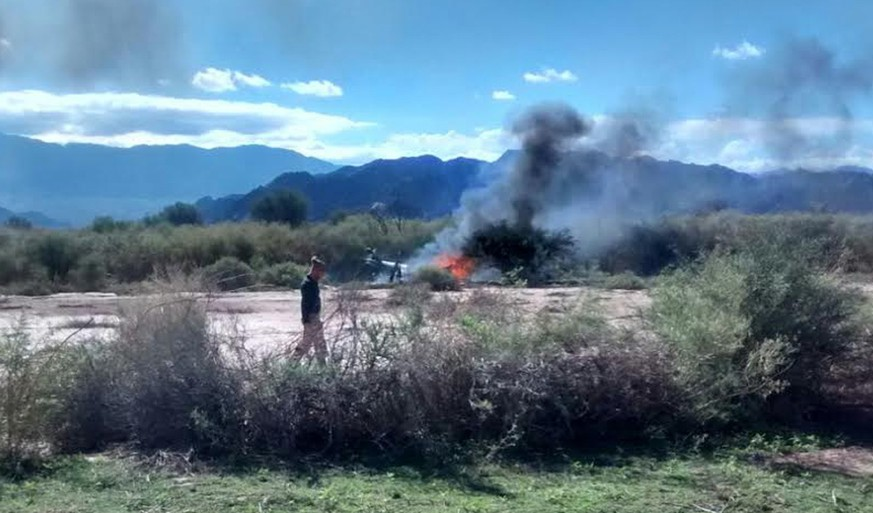 "A man stands near the smoking remains of a helicopter that crashed with another near Villa Castelli in the La Rioja province of Argentina, Monday, March 9, 2015. Two helicopters carrying passengers filming the popular European reality show ""Dropped"" crashed Monday in a remote area of northwest Argentina, killing everyone on board, authorities said. (AP Photo/Gabriel Gonzalez)"